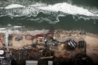 Debris from an amusement park destroyed during Superstorm Sandy lines the beach in Seaside Heights, N.J. Photo / AP
