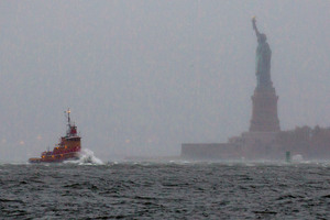 Waves crash over the bow of a tug boat as it passes near the Statue of Liberty in New York. Photo / AP