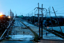 Downed power lines and a battered road is what superstorm Sandy left behind as people walk off the flooded Seaside Heights island. Photo / AP