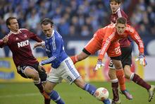 Total Football: Nuremberg's goalkeeper Patrick Rakovsky, right, and Schalke's Christian Fuchs  challenge for th