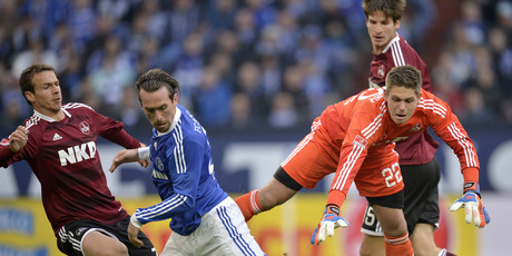 Total Football: Nuremberg's goalkeeper Patrick Rakovsky, right, and Schalke's Christian Fuchs  challenge for the ball during the German first division Bundesliga match between Schalke and Nuremberg. Photo / AP