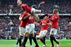 Manchester United's Robin van Persie, bottom center, is congratulated by teammates after scoring against Arsenal during the English Premier League soccer match at Old Trafford. Photo / Getty Images.