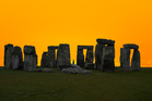 The henge at sunrise would hardly be complete without a Druid. Photo / Getty Images