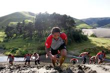 Manu Vatuvei leads players up a sand dune at Bethells yesterday. Photo / Michael Craig
