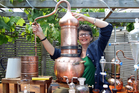 Jill Mulvaney adjusts the copper still in her garden. Photo / Doug Sherring
