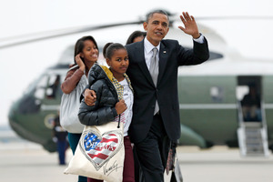 President Barack Obama walks with daughter Sasha as, first lady Michelle Obama walks with Malia. Photo / AP