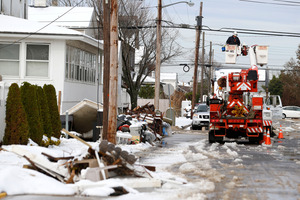 Utility workers check the power lines as snow covered debris from Superstorm Sandy lay on the side of a street following a nor'easter storm in New Jersey. Photo / AP