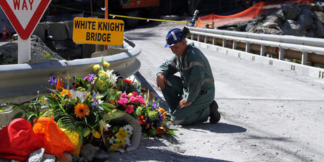 A miner laying down flowers at the White Knight Bridge near the entrance to the Pike River mine. Photo / NZPA