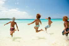 Kids cavort in the shallows of Champagne Beach. Photo / Supplied