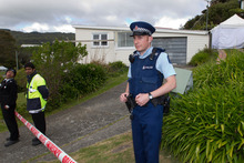 Police watch over a Tawa house where a woman's body was found.  Photo / Mark Mitchell
