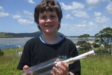 Shayde Flood, 5, with the bottle and note his father, Geoff, found on Ninety Mile Beach. The note came with a picture of the Strathnaver and was cast into the sea by Herbert Hillbrick. Photo / Supplied