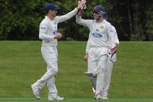 Aaron Redmond and Derek de Boorder (right) celebrate a wicket. Photo / ODT