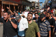 Palestinians carry the body of a militant killed during an Israeli air strike. Photo / AP