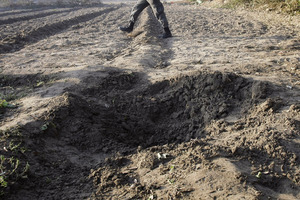 An Afghan policeman walks near a small crater caused by an impact of one of the rockets which landed in Kabul, Afghanistan.