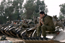 Israeli soldiers with armoured vehicles gather in a staging ground near the border with Gaza Strip.Photo / AP