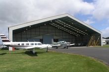 The hangar at 3 Boyd Rd, Rukihia, is for sale with other aircraft maintenance buildings (inset), alongside Hamilton Airport's runway. Photo / Supplied 
