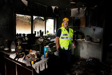 Fire investigator Gary Beer inspects the damage in a Hikurangi home after a fire believed to have originated in a drier. Photo / Michael Cunningham