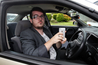 Sam Murdie with his car and iPhone. He is angry at being fined for taking a photograph of a crash scene. Photo / Doug Sherring 
