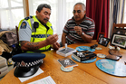 Bill Taua shows James Ranginui how the kit works during the police visit to the Fairfield area. Photo / Christine Cornege