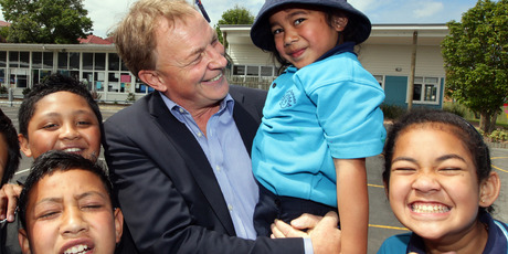 Phil Goff, holding 5-year-old Daphne Lamatia at Hay Park Primary School, is almost as busy as when he was Leader of the Opposition, but his life is far more relaxed. Photo / Doug Sherring