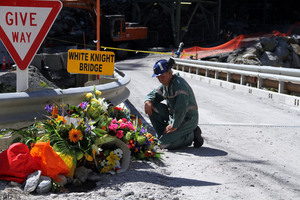 A miner laying down flowers at the White Knight Bridge near the entrance to the Pike River mine. Photo / Ross Setford