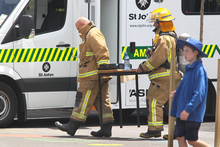 Hastings firemen carry what was believed to be the cause of an explosion or fire at Mayfiar School, Hastings. Photo / Warren Buckland