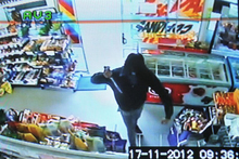 In this still shot from CCTV footage, a man brandishes a large knife during the robbery of a South Dunedin dairy on Saturday. Photo / Supplied