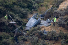 Air force investigators at work around the wreckage the 3 Squadron Iroquois helicopter which crashed in steep hill country at Pukerua Bay. Photo / Mark Mitchell