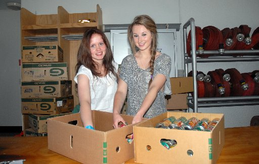 VOLUNTEERS: Sophie Bruere, 15, and Annabelle Colvin, 16, help pack groceries as part of the annual Food Bank Appeal. REACHING OUT: Times-Age commercial manager Andrew Denholm with a trolley of food which has been donated to the Masterton Foodbank, joined