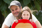 Justin Newcombe with his daughter and their DIY surfboard. Photo / Richard Robinson