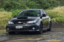 This shot shouldn't work because the day is dull, the background and foreground are cluttered and black cars often don't photograph well, but they combine to suit the brooding `bad boy' Subaru WRX very well. Photo / Phil Hanson