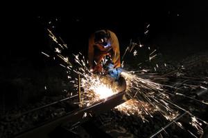 Sean Morris Sean Morris applies a high-speed spinning blade to cut the rail. Photo / Peter Calder
