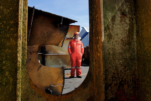 Frank Leckey, salvage master for Resolve Wreckage and Fire, stands amongst the hundreds on tons of steel removed from the ship, Rena.  Photo / APN