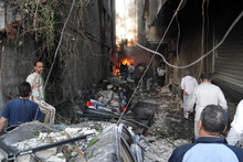 Syrian citizens gather at an alley destroyed by two cars bombs, at Jaramana neighbourhood, in the suburb of Damascus. Photo / AP