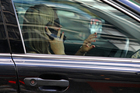 A woman speaks on her cellphone as she waits in traffic on Queen Street in Central Auckland.