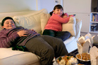 Overweight Brother and Sister Sitting on a Sofa Eating Takeaway Food and Watching the TV