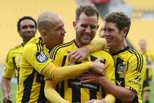 Jeremy Brockie, centre, is congratulated on scoring a goal by teammates Stein Huysegems and Tony Lochhead. Photo / AP