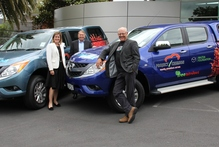 Bridget Abernethy, left, Andrew Clearwater and Project Crimson trustee Ruud Kleinpaste admire the new utes Mazda has given the trust. Photo / Supplied