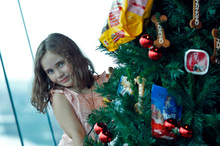 Elise Paki, 6, with her prize-winning Christmas tree, 220m above Auckland streets on a SkyCity deck. Photo / Michael Craig