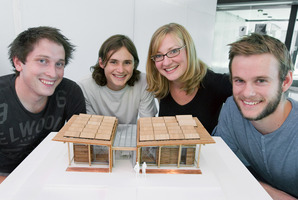 Nick Officer (left), Ben Jagersma, Anna Farrow and Eli Nuttall, with a model of the First Light energy-efficient home. Photo / Supplied