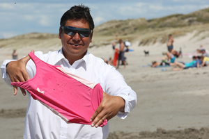 Expelled Brendan Horan displaying his daughter's oil-stained swimsuit. Photo / Mark McKeown