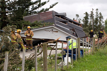 Rescue personnel survey the wreckage of a house in Hobsonville, in northwest Auckland, after the tornado whipped through yesterday afternoon. Photo / SNPA