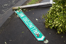 Street signage lies on the ground after a tornado hit the area of Hobsonville in West Auckland. Photo / Sarah Ivey