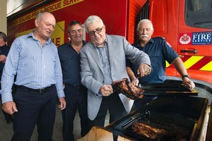 Sir Graham Henry (left) and Sir Peter Leitch assess the cooking skills of firemen Murray Selwyn (second from left) and Dick Crocker at the Christchurch Central fire station. Photo / Simon Baker
