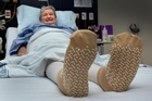 Stella Romley, who is recovering from a hip replacement, says she finds the non-slip socks 'very supportive'. Photo / Brett Phibbs