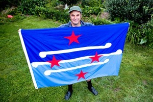 Justin Newcombe with his self-designed New Zealand flag. Photo / Dean Purcell