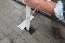 Slide a piece of aluminium or stainless steel tube into the hole in the paver to act as a sleeve.