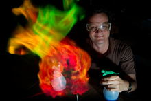 Peter Stewart, the head chemistry teacher at Papatoetoe High School, obliges the photographer with a multi-hued, photogenic fireball. Photo / Sarah Ivey
