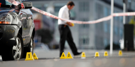 Police forensic teams investigate the crime scene on Pitt St, Auckland. Photo / Michael Craig