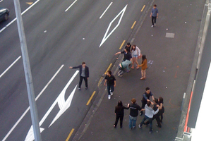 A man (on the far left) is holding what appears to be a knife outside a nightclub in central Auckland. Photo / Supplied